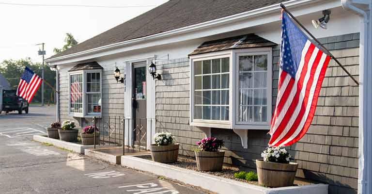 Storefront of Bagels & Beyond in West Yarmouth with American flags flying and ample parking available